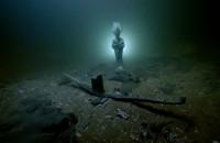 Statuette d'Osiris en bronze et barque votive en plomb posées sur les fonds sous-marin de la baie dœAboukir. Thonis-Héracléion, Égypte, VIe - IIe s. av. J.-C.. Photo : Christoph Gerigk © Franck Goddio/Hilti Foundation