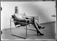 Erich Consemüller, Scène du Bauhaus : inconnue au masque dans un fauteuil tubulaire de Marcel Breuer portant un masque de Oskar Schlemmer et une robe de Lis Beyer. Photographie, 1926 © Bauhaus-Archiv Berlin